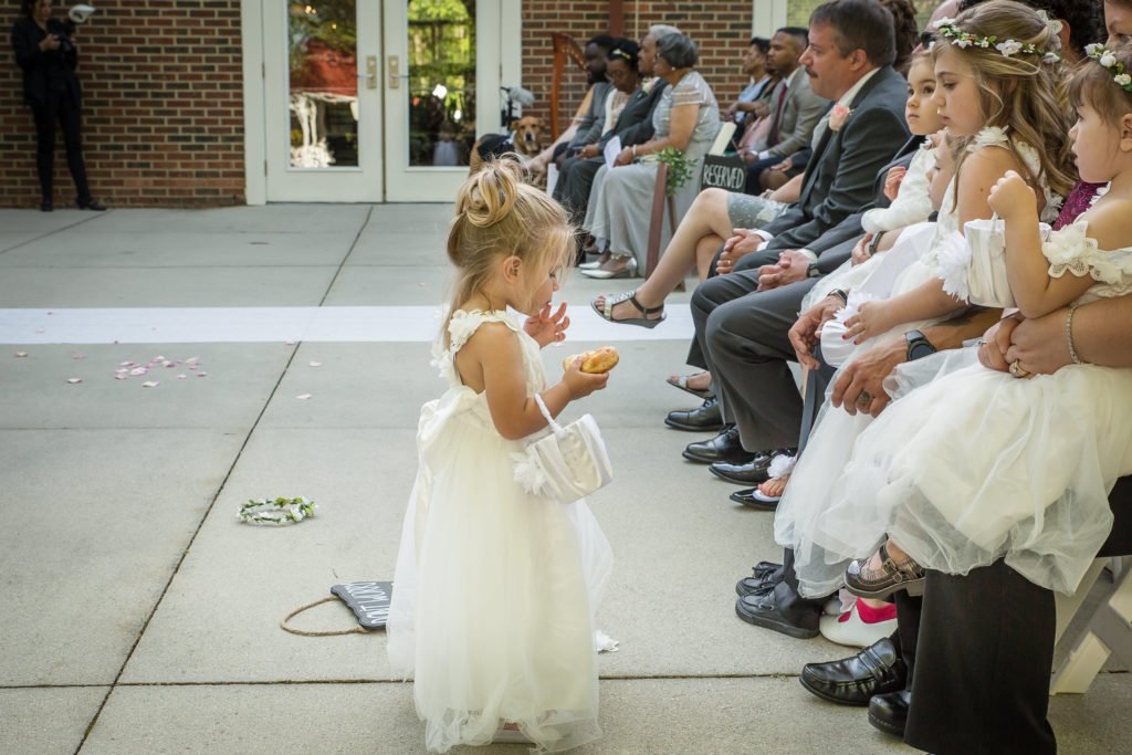 Flower girl eating donuts | Wedding photographer Raleigh NC | The Garden on Millbrook wedding