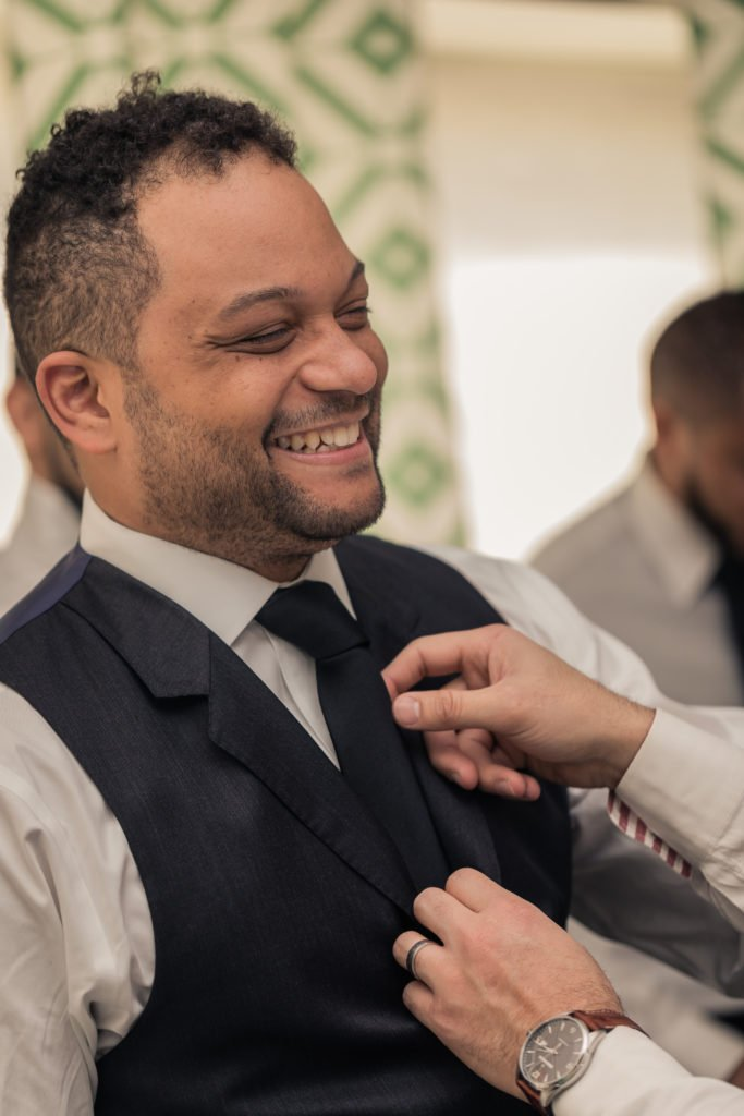 Groom having his tie adjusted by best man portrait  | Wedding photographer Raleigh NC | The Garden on Millbrook wedding