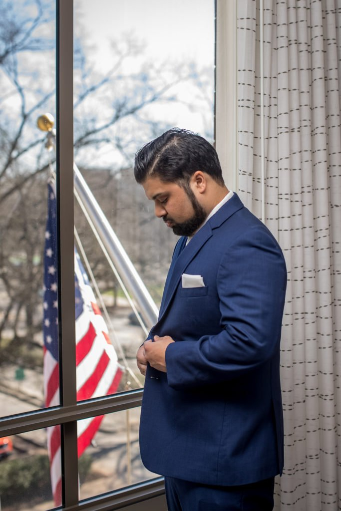 Groom getting ready with American flag on the background