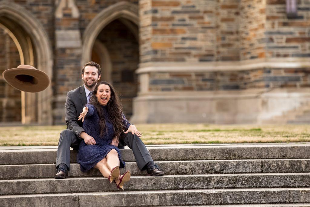 couple-smiling-throwing-hat-towards-camera-fun-engagement-photos