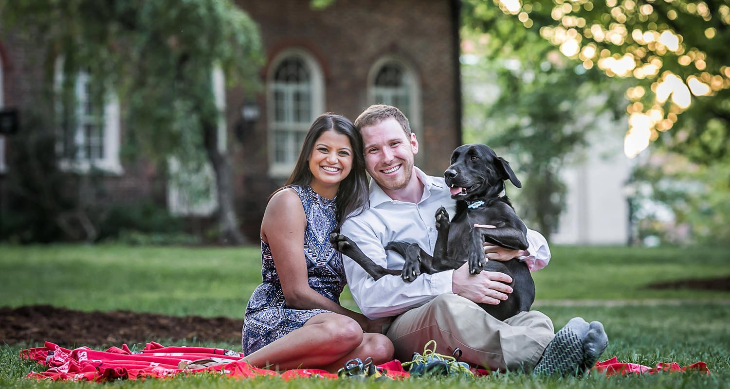 Engagement couples portrait with dog on lap | Raleigh wedding photographer