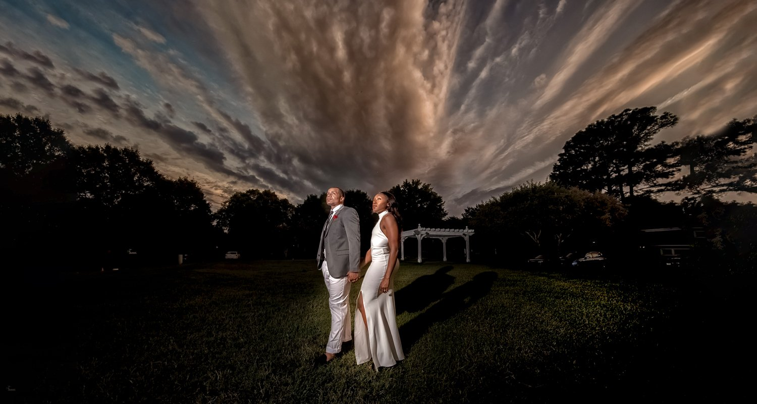 Engagement couple portrait looking at dramatic skies | Raleigh wedding photographer